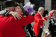 Pearly Princess hugging a Chelsea pensioner at the Pearly Kings and Queens Harvest Festival celebrations at Guildhall Yard. The annual event features early English entertainment including maypole dancing, Morris dancers and a marching band. The Chelsea pensioners & all the mayors of London take part in this traditional London event.<br /> The London tradition of the Pearly Kings and Queens began in 1875, by Henry Croft. Inspired by the local Costermongers, a close-knit group of market traders who looked after one another and were recognisable by buttons sewed onto their garments, Henry went out on the streets to collect money for charity, wearing a suit covered in pearl buttons to attract attention. When demand for his help became too much, Henry asked the Costermongers for assistance, many of whom became the first Pearly Families. Today, around 30 Pearly Families continue the tradition to raise money for various charities.