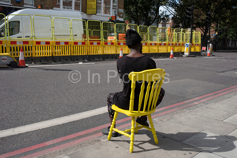 In a scene containing lots of yellow elements, a man sitting down on a bright yellow chair on the pavement along Dalston Kingsland Road in London, England, United Kingdom.