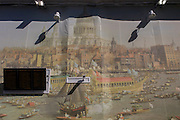 CCTV cameras and train schedule show Londoners with the background of Canaletto's 18th century painting of the Lord Mayor's Show regatta at London Bridge railway station. The  30-metre-long work of art is positioned on a temporary wall at the recently-refurbished station entrance. The picture is a reproduction of Canaletto's The Thames on Lord Mayor's Day, Reproduced at this scale commuters and tourists are be able to admire the detail of the famous painting depicting the bustling activity of the Lord Mayor's Show river procession as seen from Bankside before 1752.