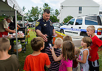 Officer Matthew Canfield hands out police cards to a group of youngsters (l-r) Calvin Hobbs, Jonathan Allen, Shelby Cheney, Jeremy Hodges, Nevelle Hodges and Dominik Allen) as they get in line for a hot dog during Laconia National Night Out Tuesday evening at Blueberry Lane Apartments.   (Karen Bobotas/for the Laconia Daily Sun)