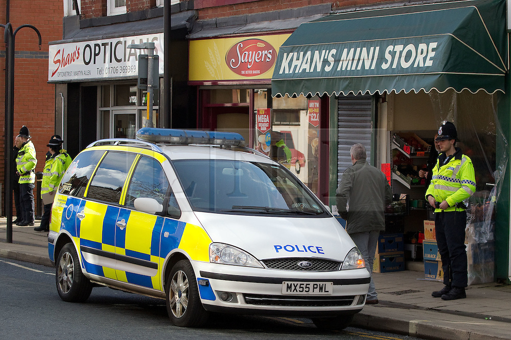 © licensed to London News Pictures. Heywood, UK  03/03/2012. Police protect an Asian-owned business in Heywood, Greater Manchester. The National Front hold a demonstration in Heywood, Greater Manchester. They protested against an alleged paedophile ring that had been operating in the area. There is currently a case being tried at Liverpool Crown Court in relation to the allegations. Last Thursday (23rd February) a protest organised in the town in relation to the same story resulted in Asian business being attacked by an angry mob. Photo credit should read Joel Goodman/LNP