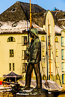 Fisher boy monument (statue),  Apotekertorget, Alesund, Norway. The town is famous for its art nouveau (Jugendstil) architecture. The  town was rebuilt after a fire in 1904. Alesund is in the heart of Fjord Country, at the entrance to Geirangerfjord on Norway's west coast.  town was rebuilt after a fire in 1904. Alesund is in the heart of Fjord Country, at the entrance to Geirangerfjord on Norway's west coast.