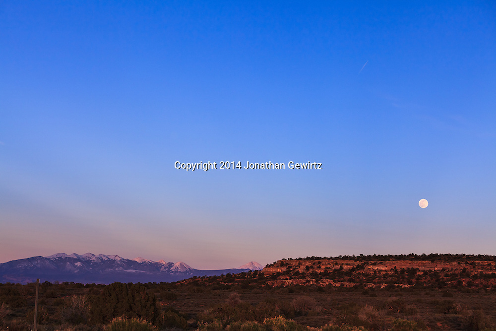 The full moon rises over the Utah desert near Moab, with peaks from the La Sal mountain range visible in the distant background.<br /> WATERMARKS WILL NOT APPEAR ON PRINTS OR LICENSED IMAGES.