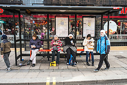 People waiting at a bus stop.