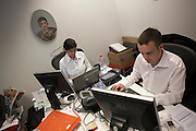 Casually-dressed accountants work in a cluttered office cubicle in an auditing company's London headquarters.