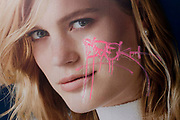 Pink graffiti tag scrawled over the face of a model, appearing on a central London fashion poster. Written over the woman's left cheek is the mark of a local teenager who has decided to leave their mark in pink on the features of the female, seen in central London.