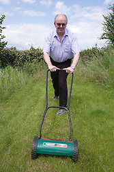 Man mowing the lawn at a city allotment,