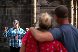 Edinburgh, Scotland, UK. 24 July, 2020. Tourists are starting to return to the Old Town in Edinburgh. A tour guide wears a face shield as she guides tourists along the Royal Mile in the historic heart of the city. Iain Masterton/Alamy Live News