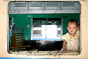 A young passenger looks out of a carriage window of a train at Mandalay station on 25th May 2016 in Myanmar