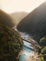 Aerial view of train crossing bridge at Katsura River Kyoto, Japan