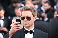 A young man takes a photo ising an iPhone on the red carpet at the Killing Them Softly gala screening at the 65th Cannes Film Festival France. Tuesday 22nd May 2012 in Cannes Film Festival, France.
