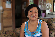 """Ena Aban, from San Joaquin village, smiles in her living room. Her husband is both a teacher and a BSCFA member. Mrs. Aban, whose oldest child is a Fairtrade-sponsored scholarship recipients, states: """"I really don't know exactly how Fairtrade works, but I want to thank them for helping us improve our community and the help they have given us, like the scholarships for our children. Belize Sugar Cane Farmers Association (BSCFA). San Joaquin, Corozal, Belize. January 23, 2013."""