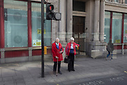 Similar-looking ladies wait to cross the road, on 30th March 2017, in London, England.