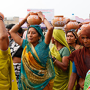Women symbolically carry earthenware pots of water on their heads.