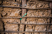 A green plastic toothbrush placed under a wooden stick which is part of the inside of a home dwelling made from traditional mud and stick in Manyara district, Tanzania, East Africa.