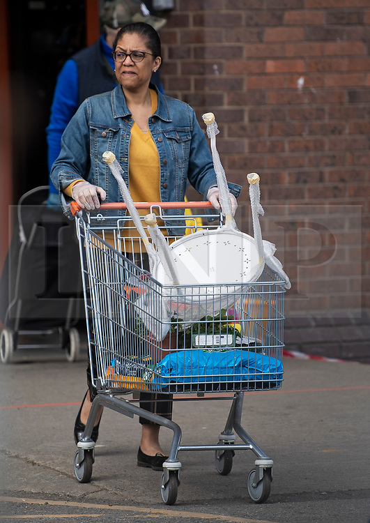 © Licensed to London News Pictures. 25/04/2020. London, UK. A shopper leaving B&Q in Cricklewood, North London with items perched in store, during Coronavirus Lockdown. The public have been told they can only leave their homes when absolutely essential, in an attempt to fight the spread of coronavirus COVID-19 disease. Photo credit: Ben Cawthra/LNP