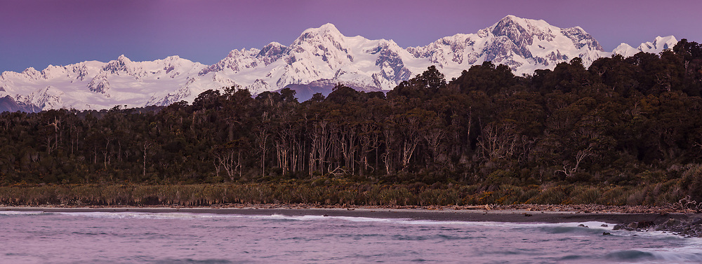Alpenglow over Southern Alps under winter snow, sunset on Mt Tasman (left) and Aoraki / Mt Cook panorama from Gillespies Beach, West Coast, New Zealand