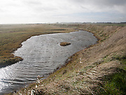 Marshland behind vegetated shingle with lagoon water bounded by costal defence sea wall, Alderton, Suffolk, England, UK