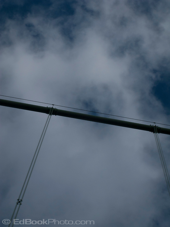 looking up at the Tacoma Narrows bridge suspension cables silhouetted against the sky. The bridge crosses the Tacoma Narrows of southern Puget Sound in western Washington state, USA