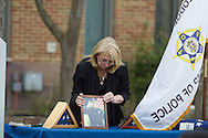 Goshen, New York - A woman adjusts the portrait of a police officer during the Orange County Law Enforcement Officer Memorial Service in front of the county courthouse on May 2, 2014. The memorial service honors the memory of the 27 members of the Orange County law enforcement community that died in the line of duty. The service also pays tribute the families and loved ones left behind for their courage, dignity and perseverance.