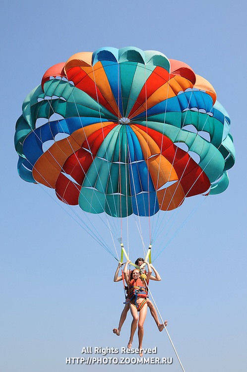 Girl and guy parasaing together on one parachute