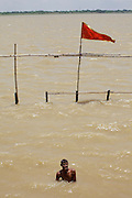Man bathing at Tulsi Ghat  by the Ganges river in Varanasi, India.