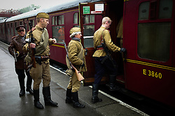 © Licensed to London News Pictures. <br /> 15/10/2016. <br /> Goathland, UK.  <br /> <br /> Re-enactors dressed in Russian military clothing climb about a train at Goathland station during the North Yorkshire Moors Railway Wartime Weekend event. <br /> The annual event brings together re-enactors and enthusiasts along the length of the NYMR heritage steam railway line to recreate the feel of the war years of the 1940's. <br /> <br /> Photo credit: Ian Forsyth/LNP