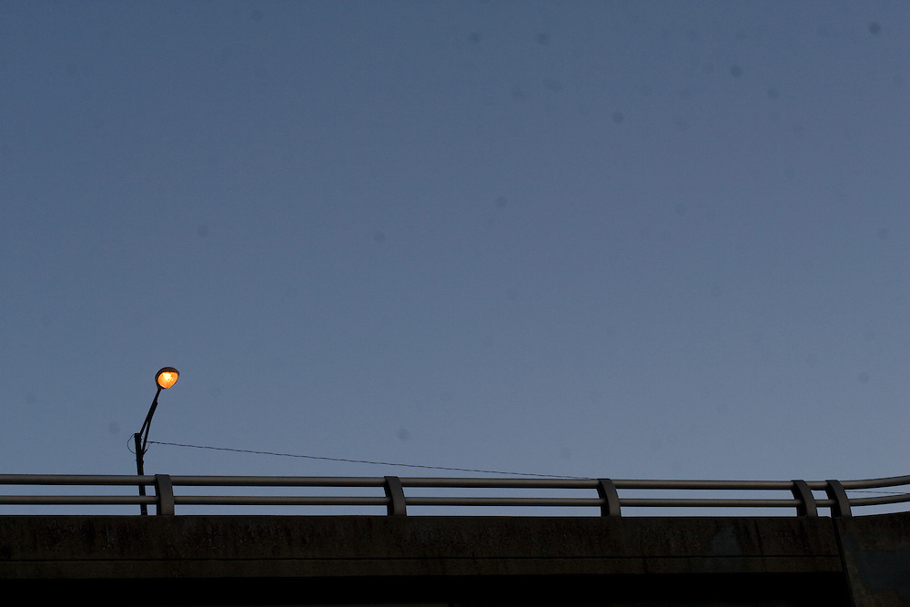 A lit street lamp on a bridge at dusk, with a bridge railing in the foreground, photographed in Charlottesville Virginia.