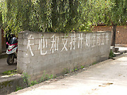 A sign written in Chinese writing on a breezeblock wall saying 'Be careful, one child policy', in the Naxi ethnic minority village of  Jiu Lian, Yunnan Province, China.