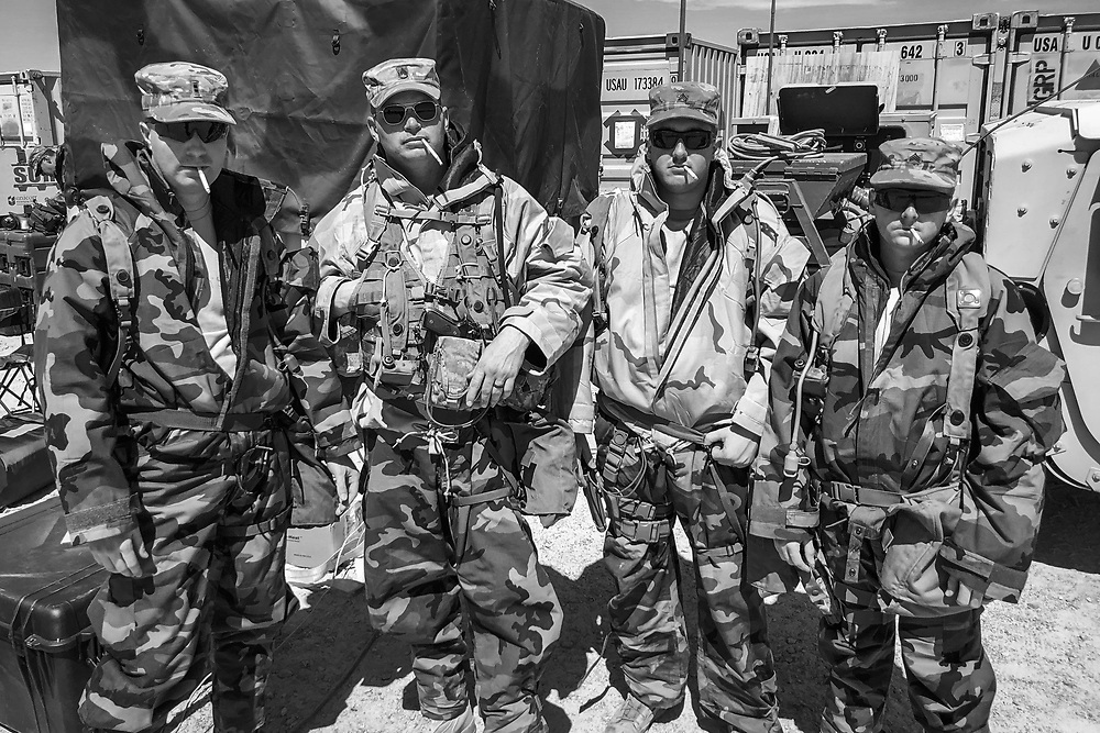 Soldiers with C Company 3-10 GSAB, 10th CAB, 10th Mountain Division take a smoke break while wearing CBRN gear during a rotation at the National Training Center in Ft. Irwin, CA.