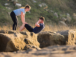 Woman holding legs of man doing crunches outdoors