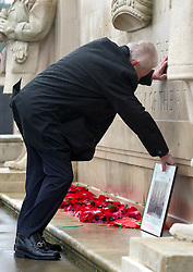 © under license to London News Pictures.  11/11/2010. A man leaves a picture at the meomorial in  Plymouth. People around the UK have observed a two-minute silence to mark Armistice day. A lone bagpipe player at a war memorial in Plymouth.