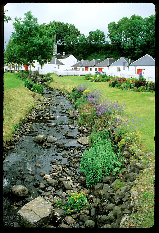 Small brook flows past red & white bldgs of Edradour Distillery, Scotland's smallest; Pitlochry Scotland