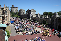 Guards of the Blues and Royals regiment and the military band march around the crowds waiting for the annual Order of the Garter Service at St George's Chapel, Windsor Castle.