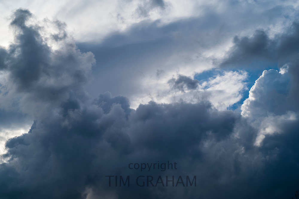 Cumulonimbus dark stormy puffy clouds in the sky and small patch of blue in skies above Gloucestershire, UK