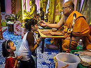 "29 MARCH 2017 - BANG KRUAI, NONTHABURI, THAILAND: A Buddhist monk annoints devotees after a ""Resurrection Ceremony"" at Wat Ta Kien (also spelled Wat Tahkian), a Buddhist temple in the suburbs of Bangkok. People go to the temple to participate in a ""Resurrection Ceremony."" Groups of people meet and pray with the temple's Buddhist monks. Then they lie in coffins, the monks pull a pink sheet over them, symbolizing their ritualistic death. The sheet is then pulled back, and people sit up in the coffin, symbolizing their ritualist rebirth. The ceremony is supposed to expunge bad karma and bad luck from a person's life and also get people used to the idea of the inevitability of death. Most times, one person lays in one coffin, but there is family sized coffin that can accommodate up to six people. The temple has been doing the resurrection ceremonies for about nine years.          PHOTO BY JACK KURTZ"