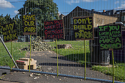 London, UK. 14th August, 2021. Signs objecting to Southwark Council's plans to develop Peckham Green as public housing are displayed on security fencing around the site. Peckham Green is a 1.4-acre public park off Peckham High Street, one of the most polluted roads in London, in a borough which is ranked fifth-worst in London and eighth-worst in the UK for easy access to green space, and local residents and campaigners have been protesting that they were not consulted by Southwark Council in relation to its plans.