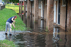 © Licensed to London News Pictures 20/07/2021. Orpington, UK. A resident trying to clear flood water from outside their home in St Pauls Cray, Orpington. Heatwave thunderstorms hit Orpington in South East London causing roads to flood and drains to overflow. Photo credit:LNP