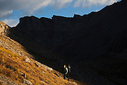 Meaghan Daly hikes into the sun below the SE Ridge of Mount Bierstadt in the Mount Evans Wilderness, Rocky Mountains Front Range, Colorado.
