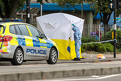 London, August 28 2017. Detectives and uniformed police work as a body lies covered in  Camden, North London following a stabbing in broad daylight at 11.45am. a 17-year-old boy has been arrested in connection with the incident and was taken to hospital.© Paul Davey.
