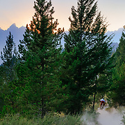Malachi Artise stirs up dry trail dust at sunset during a wildfire in the Tetons of Wyoming.