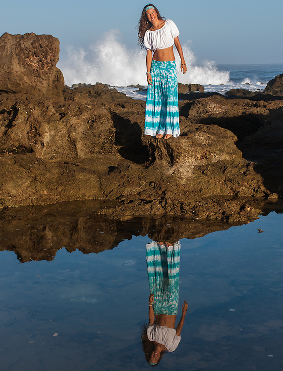 Lifestyle Portrait Woman with reflection by tide pool ocean splashing in background <br /> Noelani Studios Noelani Love