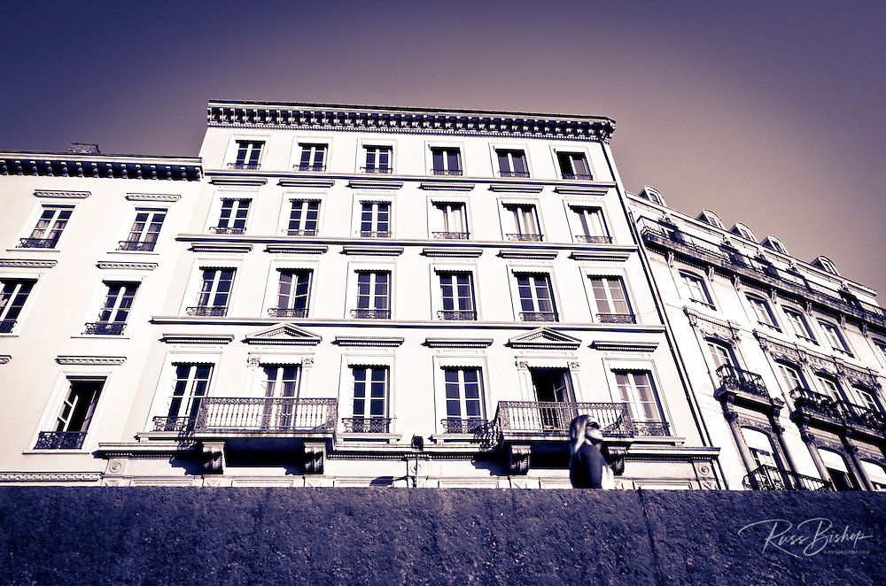Woman passing an apartment building, Lyon, France (UNESCO World Heritage Site)