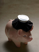 Top lit close up of a piggy bank with hot water bottle on it's head