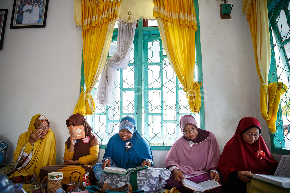 A group of women gather to read the Koran and chat, while their husband discuss matters related to their palm oil smallholdings outside the house Ukui, Riau Province, Indonesia, on 15 June 2015. This area has become dominated by palm oil production, and some smallholder farmers have formed co-operatives to share costs, increase access to markets, and become certified by the Roundtable on Sustainable Palm Oil. He is part of Amanah, a local cooperative that has helped over 400 farmers become RSPO certified - reducing their use of pesticides and fertilizers, increasing yields, and improving farm management.