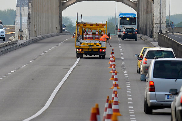 Nederland, Nijmegen, 5-5-2014Begin mei vindt noodzakelijk onderhoud aan beide Nijmeegse Waalbruggen plaats. De gemeente combineert de werkzaamheden zoveel mogelijk om langdurige verkeershinder te voorkomen. Het werk gebeurt bovendien in de rustige uren.Tussen 5 en 8 mei  wordt het asfalt op de Waalbrug gerepareerd. De werkzaamheden vinden 's avonds laat en 's nacht plaats. De brug is dan dagelijks tussen 20.00 uur en 6.00 uur gedeeltelijk afgesloten voor autoverkeer.Stadinwaarts rijden auto's en bussen over de busbaan. Vrachtverkeer wordt omgeleid via De Oversteek. Borden en verkeersregelaars informeren vrachtwagenchauffeurs. Staduitwaarts is één gewone rijbaan beschikbaar. Vrachtverkeer kan hier wel overheen.  Fietsers en voetgangers kunnen tijdens de werkzaamheden normaal gebruik maken van de brug.Foto: Flip Franssen/Hollandse Hoogte