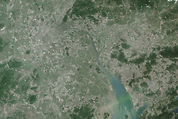 View Image Comparison<br /> View Both Images<br /> Even for a nation known for eye-popping rates of urbanization, what has happened along China's Pearl River Delta (Zhu San Jiao)<br /> over the past few decades is extraordinary.<br /> In 1988, an interlacing network of rivers and streams flowed through fertile alluvial soils full of rice paddies, wheat fields, mulberry orchards, and fish ponds. At that time, the region was mostly rural, with a population of roughly 10 million people scattered between several medium-sized cities, including Shenzhen, Guangzhou, Foshan, and Dongguan. Nearly three decades later, these cities have grown so rapidly that they have merged into an interconnected megalopolis with a population (42 million) greater than that of Australia, Argentina, or Canada.<br /> The satellite images above illustrate the dramatic growth. The bottom image was acquired by the Thematic Mapper on Landsat 5 on November 24, 1988; the top image was acquired by the Operational Land Imager on Landsat 8 on November 16, 2014. Rural areas - mainly farmland and forest - appear green. Urban areas are gray and white. Turn on the comparison tool to slide between the two images, and download the large images to observe the changes on a much finer scale.<br /> If taken as one entity, the Pearl River Delta region has overtaken Tokyo as the world's largest urban area - by size and population - according to an analysis of satellite and demographic data published by the World Bank. Between 2000 and 2010, the Pearl River Delta's urban spaces - defined as areas where the built environment covered more than 50 percent of the landscape in a given pixel - had expanded from 4,500 square kilometers to 7,000 square kilometers. (In 2010, Tokyo had a population of about 32 million people and covered about 5,600 square kilometers.) In the study, researchers used satellite data collected by the Moderate Resolution Imaging Spectroradiometer (MODIS) and land cover data from the Landsat program. They also used demographic data pr