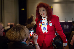 """© Licensed to London News Pictures. 14/06/2016. LONDON, UK.  A delegrate takes a photo of a Vote Leave supporter with many Vote Brexit and Vote Leave badges at the Bruges Group European referendum Brexit event in favour of """"Leave"""" on 13th June 2016. The Brexit event, was led by Lord David Owen who warned of the dangers to global stability posed by the EU withdrawing its support for NATO and committing to a European Defence Force. Owen called for a greater European commitment to NATO and the one billion euro budget of the EU's European External Action Service to be immediately transferred to NATO.  Photo credit: Vickie Flores/LNP"""