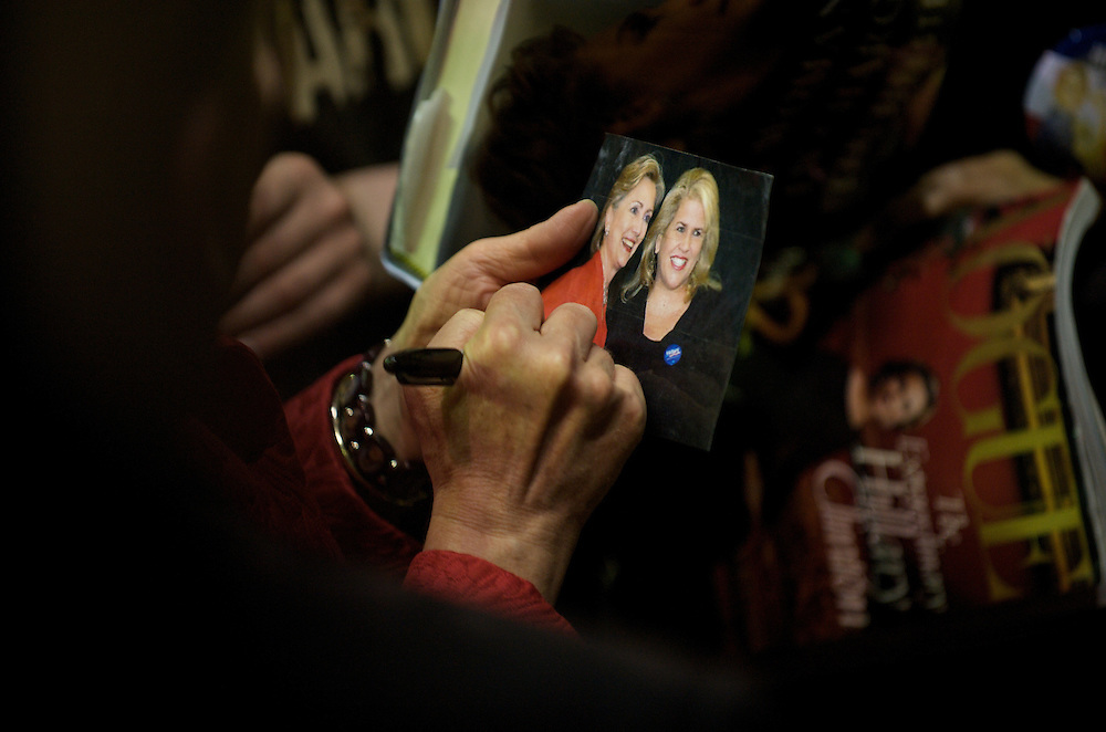 Making her way through the crowds after giving a speech, Hillary Clinton  signs a photograph of herself with a supporter at a rally in Philadelphia, Pennsylvania.