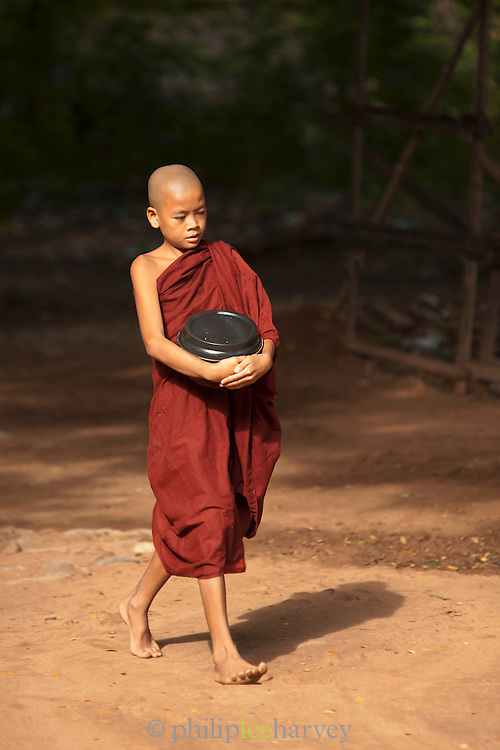 A young novice monk carries his day's food in a pot after the morning's collection in Ava, an ancient city in Myanmar